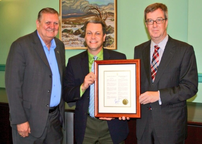 Mayor Jim Watson (r) and Orléans Ward City Councillor Bob Monette (l) present TheMensDEN.ca founder, Jean-François Claude, with the official Proclamation marking June 10, 2014 as Men's Mental Health Awareness Day in Ottawa. PHOTO: Benjamin Leikin, Ottawa Public Health.